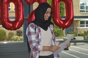 Ghufran Mohamed reads her GCSE results from a piece of paper