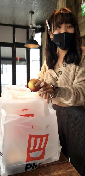 Woman is putting an apple into one of the Pho lunch bags