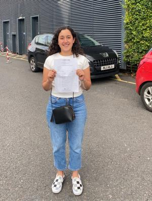 Raya Al Kubaisi stood outside a school building with her GCSE results in her hands