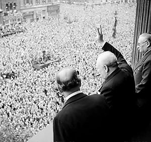 Prime Minister Winston Churchill standing on a balcony giving  the V-for-victory sign