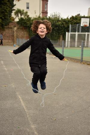 Young child jumping in the air while skipping